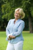 Happy senior woman smiling in the park — Stock Photo