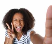 Excited young woman showing peace sign in selfie — Stock Photo