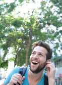 Happy young man outdoors with backpack and earphones  — Stock Photo