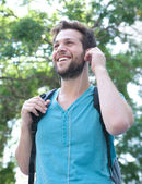 Young man smiling with backpack and earphones outdoors — Stock Photo