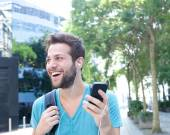 Young man smiling with mobile phone and earphones — Stock Photo