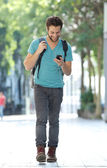 Smiling man walking in the city with mobile phone and bag — Stockfoto