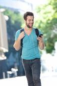 Student walking on campus with mobile phone — Foto Stock
