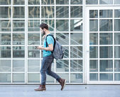 Male student walking on campus with bag and mobile phone — Foto Stock