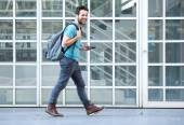 Young man walking on sidewalk with mobile phone and bag — Stockfoto