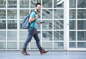 Young man walking on sidewalk with mobile phone and bag — Foto de Stock