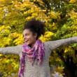 Cheerful young woman standing outdoors with arms outstretched — Stock Photo #57921163
