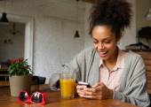 Cheerful young woman typing a text message on mobile phone — Stock Photo