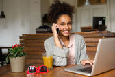 Happy young woman talking on phone at home — Stock Photo