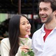 Happy couple smiling with rose outdoors — Stock Photo #61368255