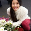 Beautiful young asian woman smiling with flowers at shop — Stok fotoğraf #61368317