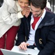 Young couple smiling and looking at laptop outdoors — Stock Photo #61368413