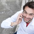 Happy young man calling by cell phone outdoors — Stock Photo #61368473