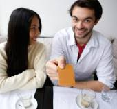 Smiling couple paying for meal at restaurant — Stock fotografie