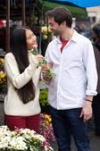 Happy young couple standing by flower shop — Stock Photo