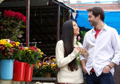 Happy young couple walking by flower shop — Stock Photo