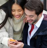 Couple smiling and looking at message on mobile phone together — Stock Photo