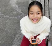 Attraktive junge Frau lächelnd mit Handy — Stockfoto