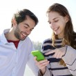 Young couple smiling and looking at mobile phone — Stok fotoğraf #61418637