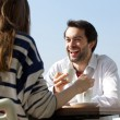 Happy man drinking coffee with woman at outdoor cafe — Stock Photo #61418683