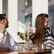 Young couple sitting at outdoor cafe asking for the bill — Stock Photo #61418721