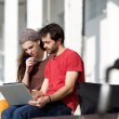 Two students sitting at campus looking at laptop together — Stock Photo #61418747