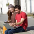 Young man and woman smiling at laptop outdoors  — Stock Photo #61418753