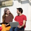 Two college students talking and working outdoors on laptop — Stock Photo #61418777