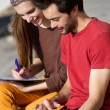 Couple students working on laptop together outdoors — Foto Stock #61418785