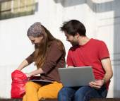 Two happy students sitting outdoors with lap top computer — Stock Photo