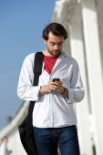 Young man with bag walking and sending text message outdoors — Stock Photo