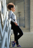 Beautiful young sports woman standing alone with earphones — Stock Photo