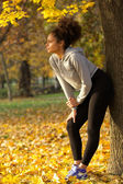 Beautiful young woman standing in park after work out — Stock Photo