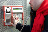 Man dialing phone number on public phone — Zdjęcie stockowe