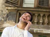 Young man laughing outdoors with mobile phone — Stock Photo