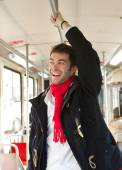 Young man smiling traveling by public transport — Stok fotoğraf