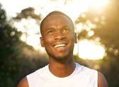 Happy young african american man smiling outdoors — Stok fotoğraf