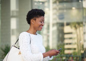 Happy african american woman reading text message — 图库照片
