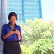 Business woman reading text message on mobile phone outdoors — Stock Photo #65612907