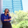 Business woman laughing on cell phone outside office building — Stock Photo #65612953