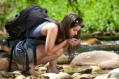 Female hiker with backpack drinking water from stream in nature — Stock Photo