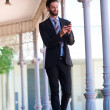 Happy businessman sending text message on mobile phone — Stock Photo #67573247