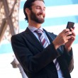 Smiling businessman sending text message on mobile phone — Stock Photo #67573255