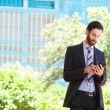 Young businessman reading text message on mobile phone — Stock Photo #67573415