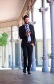 Улыбаясь бизнесмен, ходить на тротуаре с мобильного телефона — Стоковое фото