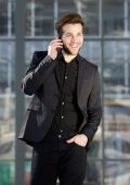 Happy young modern man talking on mobile phone — Stock Photo
