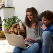 Happy brother and sister using laptop together at home — Foto de Stock   #70483879
