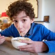 Happy boy eating noodles at home — Stock Photo #70483607