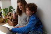 Cute boy and girl using laptop together at home — ストック写真