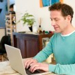 Mature male adult sitting at table at home using laptop — Stock Photo #70980333